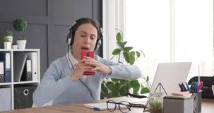 Kobieta cieszy się podczas gdy słuchający przy miejsce pracy i śpiewacka muzyka zbiory