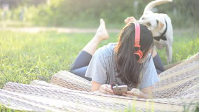 Kobieta cieszy się słuchanie muzyka hełmofonu plenerowy bawić się z życzliwym psem zbiory wideo