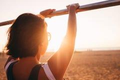 Kobieta cieszy się z zmierzchów promieniami przy plażą Obrazy Stock