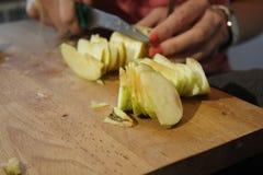 Kobieta ciie jabłka w kuchni Obrazy Stock