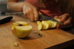 Kobieta ciie jabłka w kuchni Zdjęcia Stock