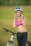 Kobieta cyklista przeciw tłu zielona trawa fotografia royalty free