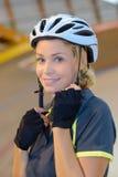 Kobieta cyklisty kładzenia hełm Zdjęcie Royalty Free