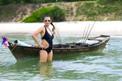 Kobieta czarny bikini szczęśliwy z małą łódką na plaży Fotografia Stock