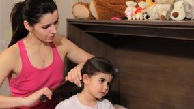 Kobieta czesze kędzierzawej dziewczyny przed iść łóżko Przygotowywa dziecka dla sen zdjęcie wideo