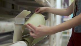 Kobieta czuje papier wallcovering w gablocie wystawowej w sklepie, zakończenie zbiory