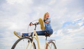 Kobieta czuje swobodnie podczas gdy cieszy się jeździć na rowerze Dziewczyna jedzie rowerowego nieba tło Najwięcej zadowalającej  obrazy stock