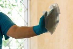 Kobieta czyści okno z błękitnymi rękawiczkami i papierowymi ręcznikami zdjęcia stock