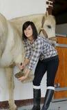 Kobieta czyści horse& x27; s kopyta Zdjęcia Stock