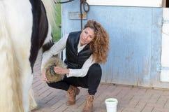 Kobieta czyści koni kopyta Zdjęcia Stock