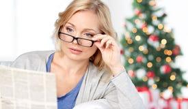 Kobieta czyta gazetę przy bożymi narodzeniami w eyeglasses Fotografia Stock
