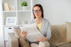 Kobieta czyta gazetę w domu w szkłach Obraz Stock