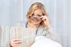 Kobieta czyta gazetę w domu w eyeglasses Fotografia Royalty Free