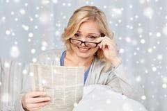 Kobieta czyta gazetę w domu w eyeglasses Obrazy Royalty Free