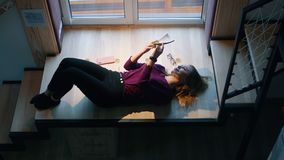 Kobieta czyta książkowego lying on the beach na schodkach okno Ucieczka rzeczywistość zdjęcie wideo