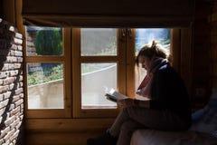 Kobieta czyta książkę okno w zima szalecie zdjęcie stock