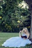 Kobieta czyta książkę opiera na drzewie w błękit sukni Fotografia Stock
