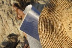 Kobieta czyta książkę z słomianym kapeluszem Fotografia Stock