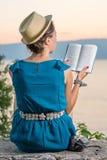 Kobieta czyta książkę z zmierzchu widokiem Fotografia Royalty Free