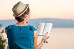 Kobieta czyta książkę z zmierzchu widokiem Obrazy Royalty Free