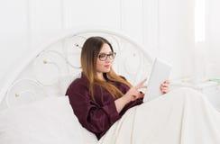 Kobieta czyta od pastylka komputeru osobistego w łóżku, kopii przestrzeń Fotografia Royalty Free