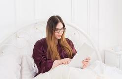 Kobieta czyta od pastylka komputeru osobistego w łóżku, kopii przestrzeń Zdjęcie Stock