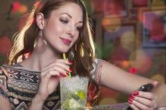 Kobieta czyta wiadomość na jej telefonie komórkowym i pije mojit Obrazy Stock