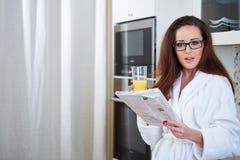 Kobieta czyta wiadomość podczas gdy pijący sok pomarańczowego zdjęcia royalty free