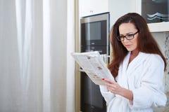 Kobieta czyta wiadomość podczas gdy pijący sok pomarańczowego fotografia stock