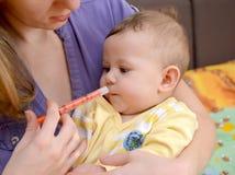 Kobieta daje chora dziecko medycyna za pomocą batcher zdjęcie stock