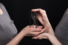 Kobieta daje hourglass jego córka odizolowywająca na czerni Obraz Stock