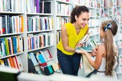 Kobieta daje książce dziewczyna w szkolnym wieku w bookstore Obraz Stock