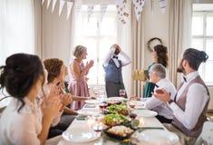 Kobieta daje prezentowi dojrzały mężczyzna na rodzinnym przyjęciu urodzinowym obrazy stock