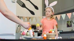 Kobieta dekoruje ciastka i dziewczyny ogląda mnie zbiory