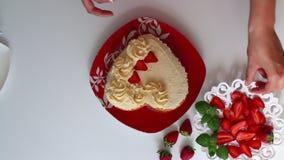 Kobieta dekoruje ciastko mażącego z śmietanką używać truskawkę Obok spodeczka jest pokrojona truskawka zbiory