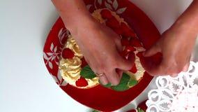 Kobieta dekoruje ciastko rozprzestrzeniającego z śmietanką używać truskawki i cytryna balsam Obok spodeczka jest pokrojona truska zdjęcie wideo