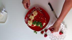 Kobieta dekoruje ciastko rozprzestrzeniającego z śmietanką używać truskawki i cytryna balsam Obok spodeczka jest pokrojona truska zbiory wideo