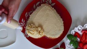 Kobieta dekoruje ciastko z kwiatami od śmietanki Używa kulinarną strzykawkę Obok spodeczka jest truskawka zbiory wideo