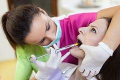 Kobieta dentysta daje jej pacjentowi anestezja zastrzykowi zdjęcie stock