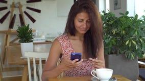Kobieta deponuje pieniądze online używać smartphone i kredytową kartę w kawiarni zbiory wideo