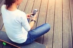 Kobieta deskorolkarza use telefon komórkowy bierze fotografię Obraz Stock