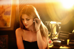 Kobieta diamentowi kolczyki stawiają dalej jej ucho Jewellery pudełko na stole obrazy stock