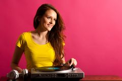 Kobieta DJ bawić się na gramofonie nad różowym tłem Zdjęcia Royalty Free