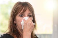 Kobieta dmucha jej nos, lekki skutek obraz royalty free