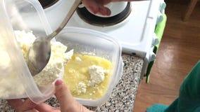 Kobieta dodaje chałupa ser zbiornik z rozciekłym masłem, wanilią i sproszkowanym cukierem, Składniki dla deseru zbiory wideo