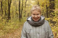 Kobieta dojrzały wiek w lesie z żółtymi liśćmi zdjęcie royalty free