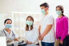 Kobieta doktorska i cierpliwi nastolatkowie patrzeje kamerę, jesteśmy ubranym ochronne maski Obraz Stock
