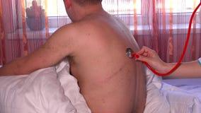 Kobieta doktorski używa stetoskop sprawdzać oddychanie pacjent z ogromną blizną zbiory wideo