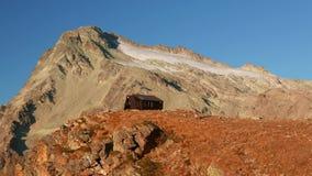 Kobieta dosięga halną budę na wierzchołku w duża wysokość skalistym krajobrazie z lodowem i szczytem w tle Przygody dalej zbiory wideo