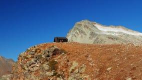 Kobieta dosięga halną budę na wierzchołku w duża wysokość skalistym krajobrazie z lodowem i szczytem w tle Przygody dalej zbiory